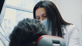 Dentiste et patient Jeune beau dentiste réparant des dents d'une belle jeune femme dans le bureau du dentiste dentiste banque de vidéos