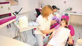 Dentiste et petite fille dans le bureau dentaire banque de vidéos