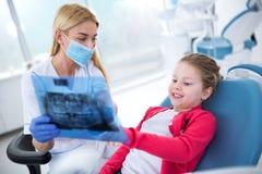 Dentiste et petite fille regardant le rayon X des dents photos libres de droits