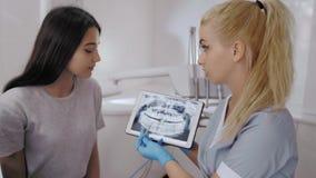 Dentiste et traitement de choix patient dans une consultation avec le matériel médical à l'arrière-plan clips vidéos
