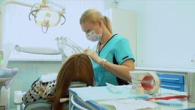 Dentiste exécutant la chirurgie utilisant l'équipement stérilisé Portrait d'un patient de The de dentiste dans la chaise dentaire banque de vidéos