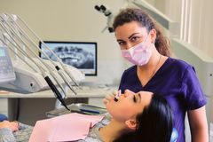 Dentiste examinant les dents femelles du ` s en art dentaire photographie stock