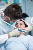Dentiste examinant les dents patientes avec un miroir de bouche image stock