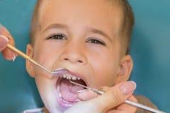 Dentiste examinant peu de boy& x27 ; dents de s dans la clinique Fermez-vous du garçon faisant examiner ses dents par un enfant d photos libres de droits