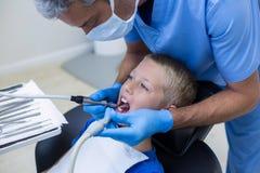Dentiste examinant un jeune patient avec des outils image libre de droits