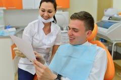 Dentiste expliquant la photo de rayon de x au patient Images libres de droits