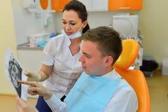 Dentiste expliquant la photo de rayon de x au patient Photographie stock libre de droits