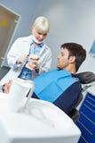 Dentiste expliquant le traitement dentaire avec des dentiers Images stock