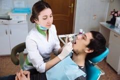 Dentiste féminin avec le patient masculin au bureau dentaire Concept de sain photos stock