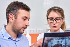 Dentiste féminin caucasien expliquant au patient masculin le rayon X image stock