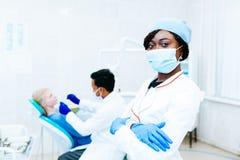 Dentiste féminin de jeune Afro-américain dans le masque devant le dentiste vérifiant des dents au patient à la clinique Clinique  photo libre de droits