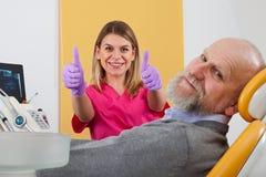 Dentiste féminin de sourire avec le patient photographie stock libre de droits