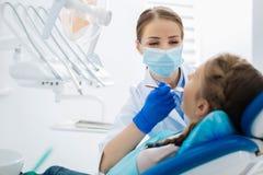 Dentiste féminin positif étant au travail images stock