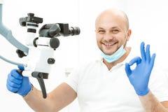 Dentiste faisant le signe fin près du microscope dentaire photographie stock libre de droits