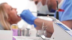 Dentiste focalisé avec la perceuse dentaire nettoyant les dents du mauvais patient banque de vidéos