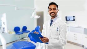 Dentiste indien avec le presse-papiers au-dessus de la clinique dentaire images libres de droits