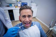 Dentiste injectant des anesthésiques dans la bouche patiente masculine effrayée image stock