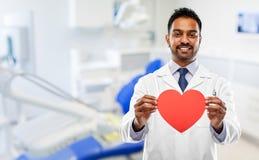 Dentiste masculin avec le coeur rouge à la clinique dentaire photographie stock libre de droits