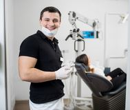 Dentiste masculin de sourire avec les accolades en céramique tenant les outils dentaires photos stock