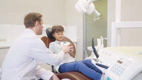 Dentiste masculin instruisant peu de garçon au sujet d'hygiène dentaire banque de vidéos