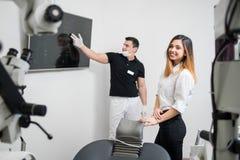 Dentiste masculin montrant au patient féminin son image dentaire de rayon X sur l'écran d'ordinateur dans le bureau dentaire photo libre de droits