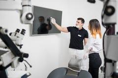 Dentiste masculin montrant au patient féminin son image dentaire de rayon X sur le moniteur d'ordinateur dans une clinique dentai photo libre de droits