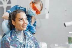 Dentiste mettant sur le tablier en plastique sur la cliente de sourire de femme images stock