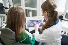 Dentiste montrant les détails de la photo de rayon X au patient féminin dans le bureau dentaire Foyer sur les femmes dentistry images stock