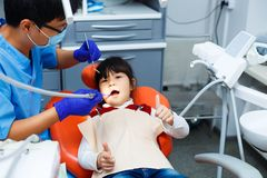 Dentiste nettoyant des dents du ` s de petite fille Le jeune patient est calme et images libres de droits