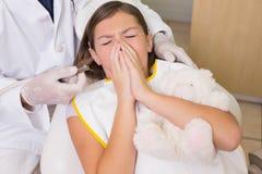 Dentiste pédiatrique essayant de voir les dents de éternuement de patients Image stock