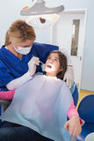 Dentiste pédiatrique examinant son jeune patient Images stock