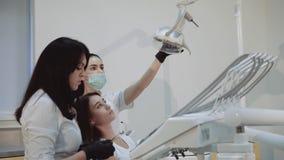 Dentiste praparing pour le traitement et la fille de consultation 4K banque de vidéos