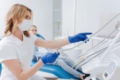 Dentiste professionnel capable sélectionnant l'outil images libres de droits