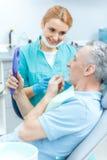 Dentiste professionnel regardant le miroir se tenant patient mûr images libres de droits