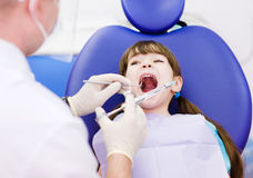 Dentiste retenant une seringue et anesthésiant son patient Photo stock