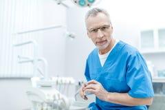 Dentiste supérieur dans l'uniforme avec le modèle de mâchoires Photo stock