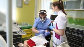 Dentiste traitant des dents du ` un s de patient avec les outils dentaires dans la clinique dentaire dentistry banque de vidéos