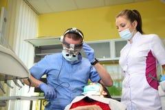 Dentiste traitant des dents du ` un s de patient avec les outils dentaires dans la clinique dentaire dentistry photos libres de droits