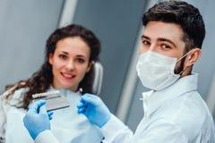 Dentiste vérifiant et choisissant la couleur des dents de la jeune femme regardant la fin de caméra vers le haut de la vue Foyer  photographie stock