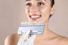 Dentiste vérifiant la couleur des dents de la jeune femme images stock