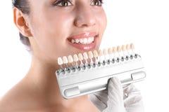 Dentiste vérifiant la couleur des dents de la jeune femme sur le fond blanc photographie stock