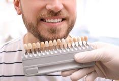 Dentiste vérifiant la couleur des dents du jeune homme images libres de droits