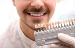 Dentiste vérifiant la couleur des dents du jeune homme images stock