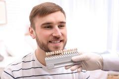 Dentiste vérifiant la couleur des dents du jeune homme photos stock