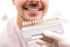 Dentiste vérifiant la couleur des dents du jeune homme photographie stock