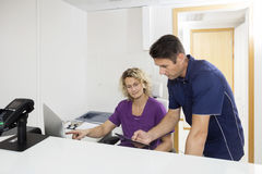 Dentistes à l'aide des ordinateurs à la réception dans l'hôpital Image stock