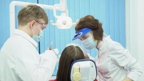Dentistes d'homme et de femme dans les masques et les lunettes medias Dentistes d'associés dans l'uniforme stérile protecteur ave banque de vidéos