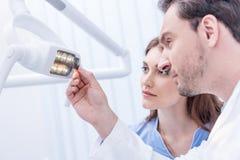 Dentistes regardant la photo de rayon X des dents à disposition contre la lampe dentaire photographie stock