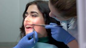 Dentisti che installano i ganci dei denti video d archivio