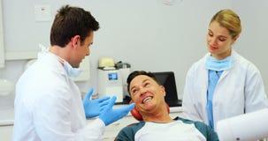 Dentisti che interagiscono con un paziente maschio video d archivio